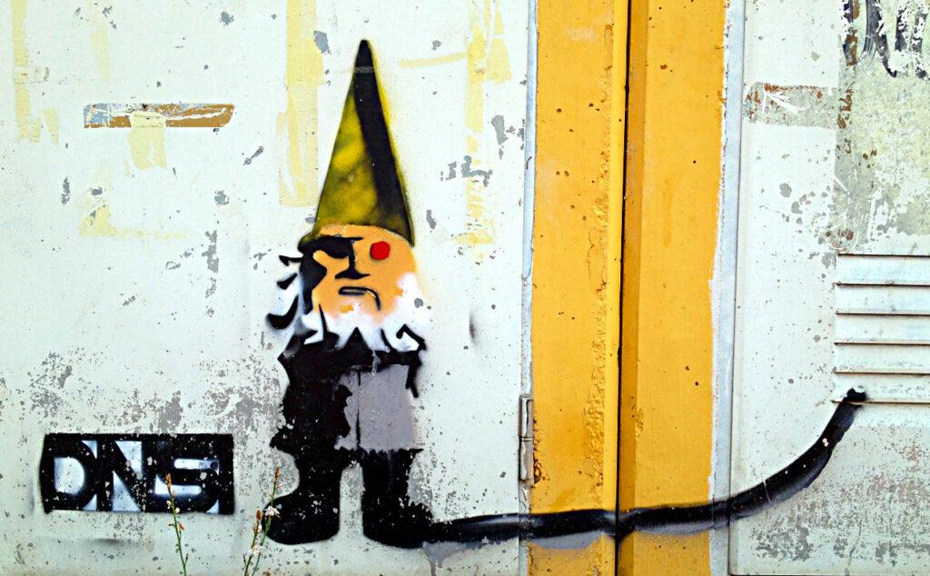 Graffito eines Zwergs mit steiler grüner Mütze, frontal neben gelben Streifen. Er trägt ein rotes Auge neben schattierter rechter Körperseite. Der linke Fuß zieht einen schwarzen Balken nach rechts im Bild.